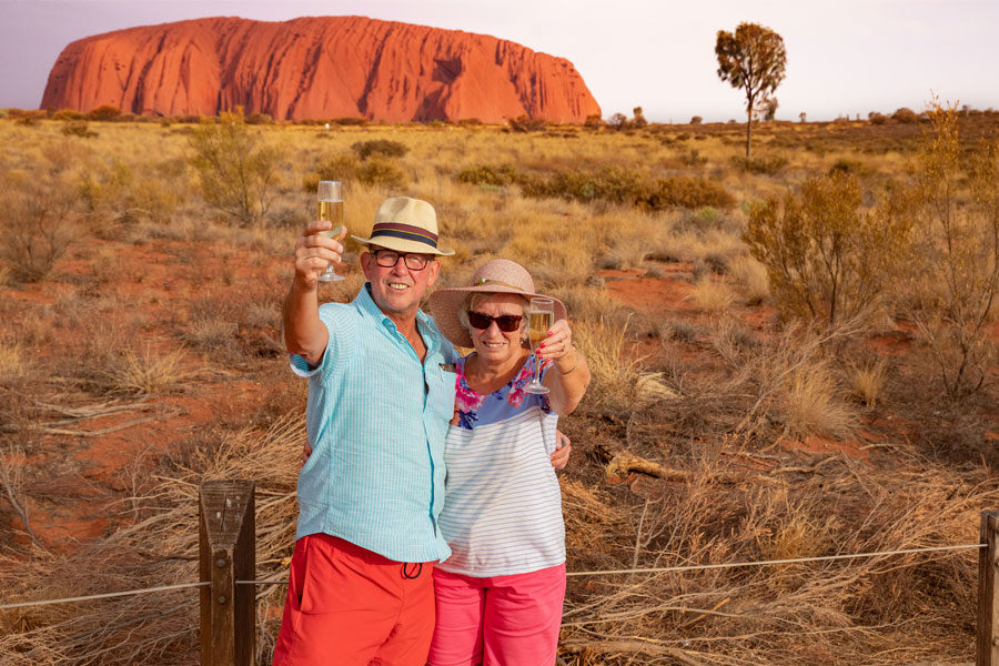 Couple enjoy a glass of sparkling wine during their Uluru tour operated by Emu Run Experience